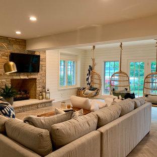 Idée de décoration pour un grand sous-sol tradition donnant sur l'extérieur avec un mur blanc, un sol en carrelage de porcelaine, une cheminée standard, un manteau de cheminée en pierre et un sol gris.