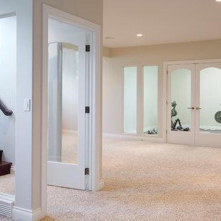 Cette image montre un grand sous-sol minimaliste semi-enterré avec un mur beige, moquette et une cheminée ribbon.