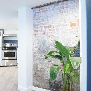 Réalisation d'un petit sous-sol minimaliste semi-enterré avec un mur blanc, sol en stratifié, aucune cheminée, un manteau de cheminée en brique et un sol gris.