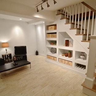 Cette image montre un sous-sol chalet enterré et de taille moyenne avec un mur blanc, un sol en bois clair, aucune cheminée et un sol marron.