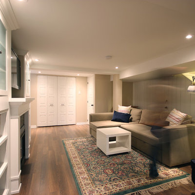 Basement - mid-sized traditional underground brown floor and dark wood floor basement idea in Ottawa with beige walls, a standard fireplace and a brick fireplace