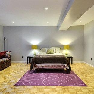 Idée de décoration pour un grand sous-sol design donnant sur l'extérieur avec un mur gris et un sol en bois clair.