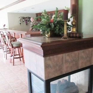 Foto di un'ampia taverna chic con sbocco, pareti verdi, pavimento con piastrelle in ceramica, camino classico e cornice del camino piastrellata
