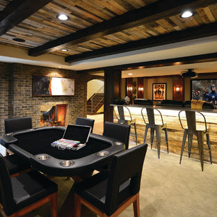 Cette image montre un très grand sous-sol design avec moquette, une cheminée double-face, un manteau de cheminée en brique, un sol gris, un mur marron et salle de cinéma.