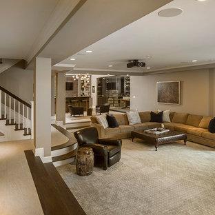 Idées déco pour un très grand sous-sol romantique donnant sur l'extérieur avec un mur beige, un sol en bois foncé, une cheminée standard, un manteau de cheminée en pierre et un sol marron.