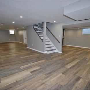 Aménagement d'un sous-sol classique enterré et de taille moyenne avec un mur gris, un sol en vinyl et un sol marron.