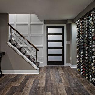 Großes Modernes Untergeschoss mit dunklem Holzboden, grauer Wandfarbe und braunem Boden in New York