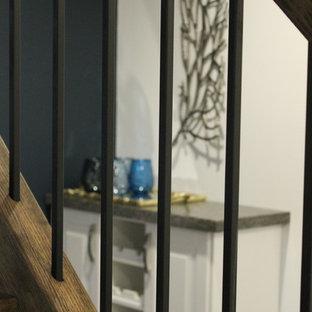 Cette photo montre un sous-sol éclectique avec un mur blanc, moquette, cheminée suspendue et un sol gris.