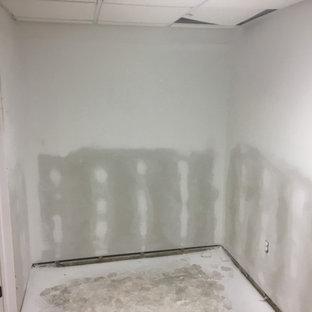 Idées déco pour un grand sous-sol classique enterré avec un mur jaune, sol en stratifié et un sol gris.