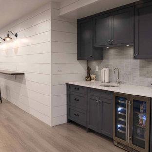 ニューヨークの中くらいのトランジショナルスタイルのおしゃれな地下室 (グレーの壁、ラミネートの床、暖炉なし、茶色い床、半地下 (窓あり) ) の写真
