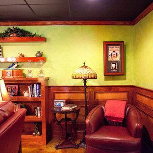 Idées déco pour un grand sous-sol éclectique avec un mur vert, un sol en bois foncé, une cheminée standard et un manteau de cheminée en pierre.
