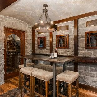 Exemple d'un grand sous-sol chic avec un mur gris, un sol en bois brun et un sol marron.
