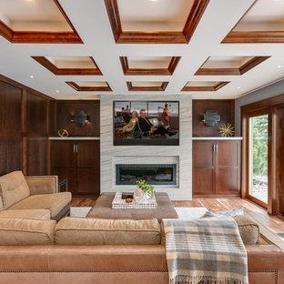 Cette image montre un sous-sol traditionnel donnant sur l'extérieur avec un mur marron, une cheminée ribbon et un sol en bois brun.