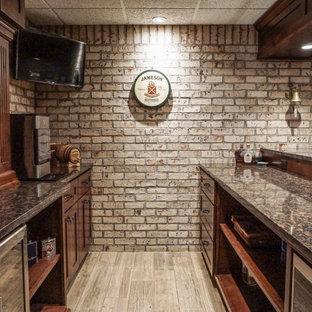 Aménagement d'un petit sous-sol montagne donnant sur l'extérieur avec un bar de salon, un mur blanc, un sol en bois clair, une cheminée double-face, un manteau de cheminée en brique, un sol gris et un mur en parement de brique.