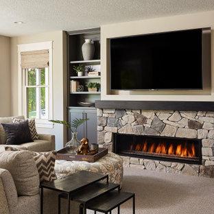 Aménagement d'un grand sous-sol classique donnant sur l'extérieur avec un mur gris, moquette, une cheminée ribbon, un manteau de cheminée en pierre et un sol gris.