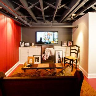 Aménagement d'un sous-sol éclectique enterré et de taille moyenne avec un mur rouge, béton au sol, aucune cheminée et un sol rouge.