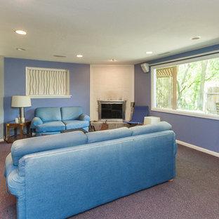 Idée de décoration pour un sous-sol tradition semi-enterré et de taille moyenne avec un mur gris, moquette, une cheminée d'angle et un sol violet.