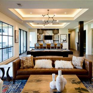 Idée de décoration pour un très grand sous-sol design donnant sur l'extérieur avec un mur beige, un sol en bois brun et un sol marron.