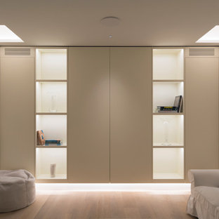 Photo of a medium sized contemporary basement in London with white walls and light hardwood flooring.