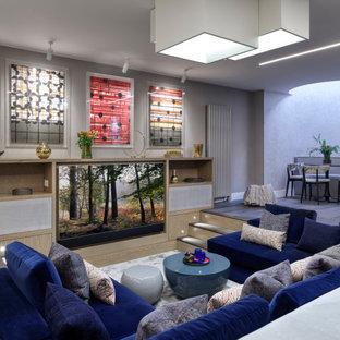 Cette image montre un grand sous-sol design enterré avec salle de cinéma, un mur gris, un sol en bois clair et un sol beige.