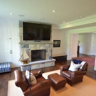 Inspiration pour un sous-sol traditionnel donnant sur l'extérieur avec un mur blanc, un sol en bois foncé, un poêle à bois, un manteau de cheminée en pierre et un sol marron.