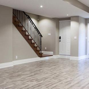 Immagine di una grande taverna minimalista interrata con pareti grigie, pavimento in laminato, camino classico, cornice del camino in mattoni e pavimento grigio