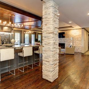 Inspiration pour un grand sous-sol traditionnel donnant sur l'extérieur avec un mur gris, un sol en ardoise, une cheminée standard, un manteau de cheminée en pierre et un sol multicolore.