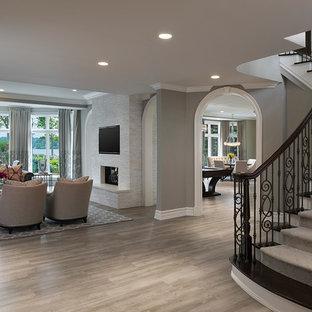 Cette image montre un très grand sous-sol traditionnel donnant sur l'extérieur avec un mur gris, un sol en carrelage de céramique, une cheminée standard et un manteau de cheminée en pierre.