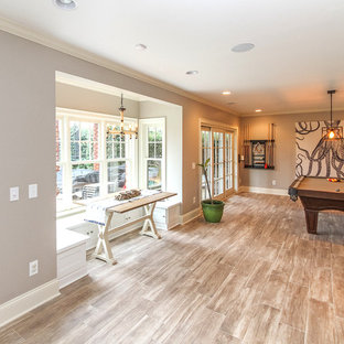 Example of a mid-sized transitional walk-out ceramic floor basement design in Charlotte with gray walls and no fireplace