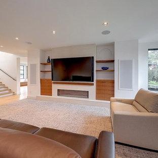 Inspiration pour un grand sous-sol design donnant sur l'extérieur avec un mur blanc, un sol en bois clair, une cheminée ribbon, un manteau de cheminée en plâtre et un sol beige.