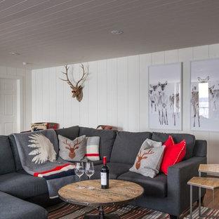 Aménagement d'un sous-sol bord de mer donnant sur l'extérieur et de taille moyenne avec un mur blanc et un sol en bois brun.