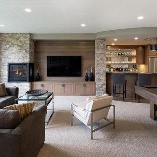 Imagen de sótano con ventanas tradicional renovado, de tamaño medio, con paredes grises, moqueta, chimenea de esquina, marco de chimenea de piedra y suelo beige