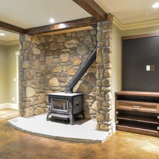 Exemple d'un grand sous-sol montagne enterré avec un mur gris, béton au sol, un poêle à bois, un manteau de cheminée en pierre et un sol marron.