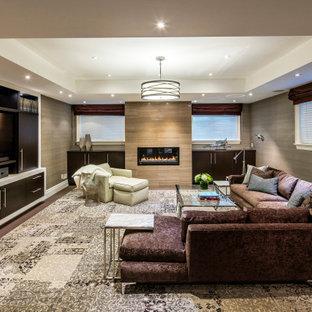 Exemple d'un grand sous-sol tendance semi-enterré avec salle de cinéma, un mur multicolore, moquette, cheminée suspendue, un manteau de cheminée en pierre, un sol multicolore, un plafond voûté et du papier peint.