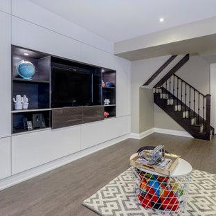 Réalisation d'un petit sous-sol minimaliste semi-enterré avec salle de cinéma, un mur beige, sol en stratifié et un sol marron.