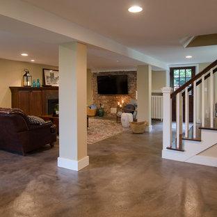 Idee per una taverna stile americano di medie dimensioni con sbocco, pareti beige, pavimento in cemento, cornice del camino piastrellata, pavimento grigio e camino classico
