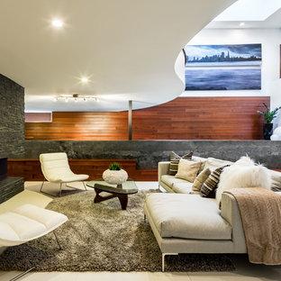 Cette image montre un grand sous-sol design donnant sur l'extérieur avec un mur blanc, un sol en carrelage de céramique, une cheminée double-face, un sol beige et un manteau de cheminée en pierre.