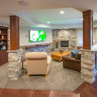 Idées déco pour un grand sous-sol classique enterré avec un mur blanc, un sol en bois brun, une cheminée d'angle, un manteau de cheminée en pierre et un sol marron.