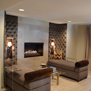 Photo of a contemporary look-out basement in Indianapolis with beige walls, a ribbon fireplace, a tiled fireplace surround, light hardwood flooring and beige floors.