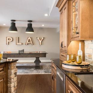Inspiration pour un grand sous-sol traditionnel avec un mur beige, un sol en vinyl, une cheminée standard, un manteau de cheminée en pierre et un sol marron.