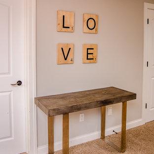 Inspiration pour un sous-sol bohème donnant sur l'extérieur et de taille moyenne avec un mur gris, moquette, cheminée suspendue et un sol beige.