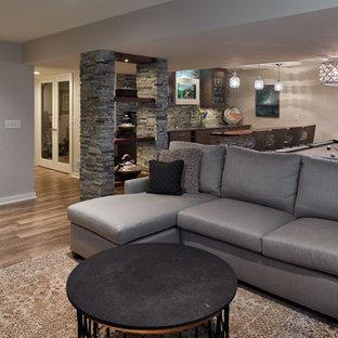 Aménagement d'un sous-sol classique semi-enterré et de taille moyenne avec un mur gris, un sol en vinyl, une cheminée ribbon, un manteau de cheminée en pierre et un sol marron.