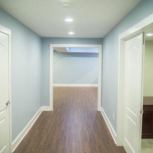 Cette image montre un très grand sous-sol design enterré avec un mur bleu, un sol en carrelage de porcelaine et aucune cheminée.