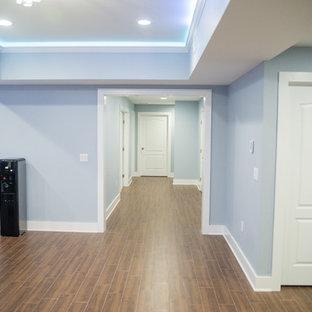 Réalisation d'un très grand sous-sol design enterré avec un mur bleu, un sol en carrelage de porcelaine et aucune cheminée.