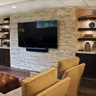 Cette photo montre un grand sous-sol chic avec un mur beige, sol en stratifié et un sol marron.