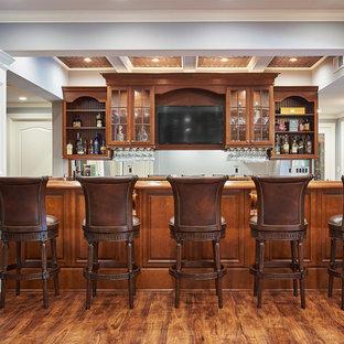 Exemple d'un sous-sol chic avec un bar de salon, un sol en bois brun et un plafond à caissons.