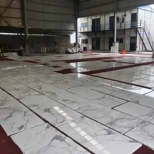 Inspiration pour un sous-sol minimaliste donnant sur l'extérieur et de taille moyenne avec un mur blanc, un sol en marbre et un sol blanc.