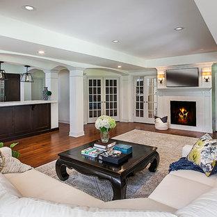 Idée de décoration pour un grand sous-sol tradition donnant sur l'extérieur avec un mur gris, un sol en bois brun, une cheminée standard et un manteau de cheminée en bois.