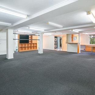Exemple d'un grand sous-sol tendance donnant sur l'extérieur avec salle de jeu, un mur blanc, moquette, un sol noir et un plafond en poutres apparentes.