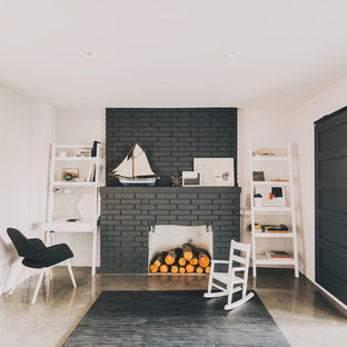 Photo of a medium sized midcentury walk-out basement in Seattle with white walls, concrete flooring, a standard fireplace and a brick fireplace surround.